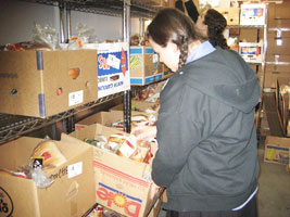 A young woman helping gather food for the needy at a Tomchei shabbas warehouse