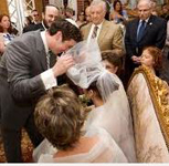 Chosson (groom) placing the veil on the kallah(bride)