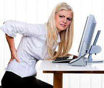 A woman not sitting correctly at her computer suffering with low back pain