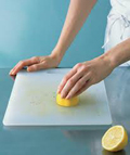 A woman cleaning cutting board with a lemon