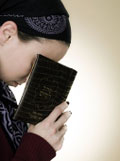 Young girl concentrating on saying Tehilim (Psalms) for someone who is ill or injured
